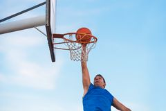 Street basketball athlete performing slam dunk on the court.  stock photos