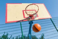 Street basketball, close-up of basketball ring and ball flying into the basket stock image
