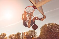 Street basketball player performing power slum dunk royalty free stock photo
