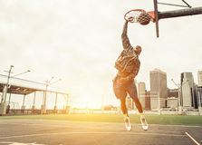 Street basketball player performing power slum dunk Stock Image