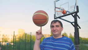 Basketball Player With a Ball. Street basketball player turns the ball balancing on the finger stock video
