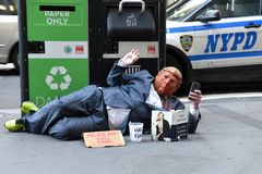 Street beggar wears a Trump mask and reading the book of Hillary Clinton What Happened. stock photos