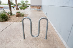 Street bike parking - metal racks against gray building Royalty Free Stock Images