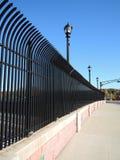 Street and a black steel fence. Closeup Street and a black steel fence Royalty Free Stock Photos