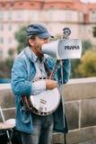 Street Busker performing jazz songs at the Charles Bridge. PRAGUE, CZECH REPUBLIC - OCTOBER 10, 2014: Street Busker performing jazz songs at the Charles Bridge Stock Photo