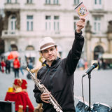 Street Busker performing jazz songs at the Old. PRAGUE, CZECH REPUBLIC - OCTOBER 10, 2014: Street Busker performing jazz songs at the Old Town Square in Prague Stock Image