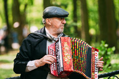 Street Busker performing songs in city park in Stock Photography