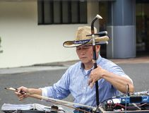 Street Busker Plays the Chinese Fiddle. KAOHSIUNG, TAIWAN -- FEBRUARY 16, 2018: A street musician plays the erhu, a two-stringed Chinese fiddle, with a long bow Royalty Free Stock Photo