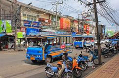 Street with busses, Thailand. Street in historic Phuket town with colorful shops and advertisements, typical local busses,open electric networks and motorbikes Royalty Free Stock Image