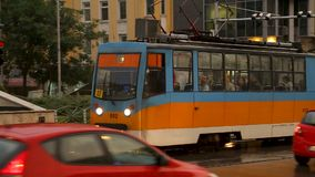 Street with busy traffic, tram running in middle of road, public transportation. Stock footage stock video