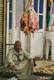 Street Butcher. A man in traditional clothing selling meat and vegetables on the street in Egypt