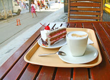 Street cafe. Cup of coffee and piece of cake on the dinner-wagon of street cafe royalty free stock photo