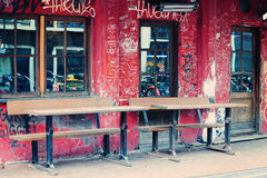 Street cafe in Amsterdam with graffiti on the shabby wall. Street cafe in Amsterdam with graffiti on the shabby red brown wall and reflections of bikes in the Stock Photo