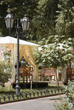 Street cafe interior in a city park, green trees and bright sun in summer, brown toned Stock Photo
