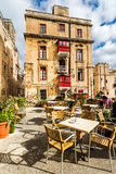 Street cafe in Malta. Outdoor with tables and chairs and beautiful building behind Stock Image
