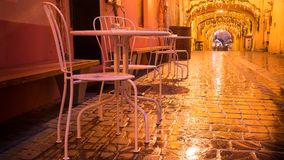 Street cafe at the night against city illumination lights royalty free stock image