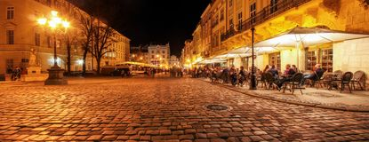 Street cafe on the old streets of the night city. Lviv city in old town market square with illuminated night people  sitting at the tables in the cafe. long royalty free stock photos
