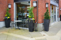 Street cafe for two at the shop window. Flowerbeds, marble table, and two chairs as a small cafe outside stock photos