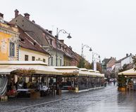 Street cafes and restaurants in rainy day in the Nicolae Balcrscu street in Sibiu city in Romania. Sibiu, Romania, October 07, 2017 : Street cafes and Stock Images