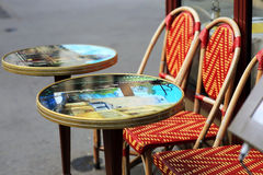 Street cafes with round tables in Paris. Street cafes with round tables, glass top with pictures and red chairs Royalty Free Stock Image