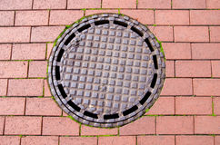 Street canalization steel manhole on pavement Royalty Free Stock Photos