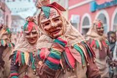 Friendly carnaval figure in brown, green, red robe shows hand gesture. Carnival in southern Germany - Black Forest stock image