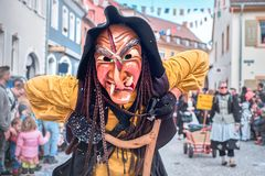 Ugly witch in yellow robe looks into the camera. Street carnival in southern Germany - Black Forest royalty free stock photo