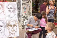 Street cartoonist draws a caricature. Tel Aviv, Israel - April 28, 2016: Street cartoonist draws a caricature surrounded by people in Tel Aviv, Isarel royalty free stock photography