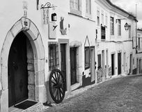 A street within the castle, with typical houses and a wheel - in black and white stock photography