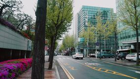 A street in the center of Seoul in Korea with people walking along the street along the road