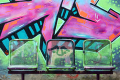 Street chairs in front of graffiti wall. Three painted street chairs in front of graffiti wall on a schoolyard royalty free stock images