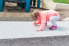 Street charlk art. Toddler drawing with chalk on paved walk near playground Royalty Free Stock Images