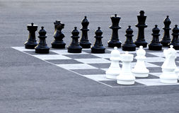 Street chess. Oversized chess pieces and painted board on asphalt royalty free stock photos