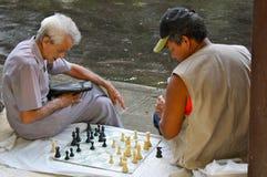 Street Chess, Havana, Cuba. Two cuban men playing chess on a sidewalk after heavy shower. August 2010, Havana Royalty Free Stock Image
