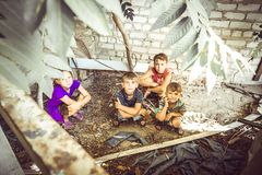 Street children sit in the trash in the corner of an abandoned house. Staged photo.  royalty free stock photo