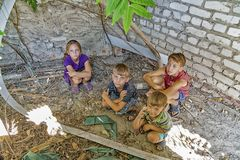Street children sit in the trash in the corner of an abandoned house. Staged photo.  royalty free stock photography