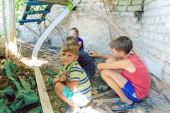 Street children sit in the trash in the corner of an abandoned house. Staged photo.  royalty free stock image