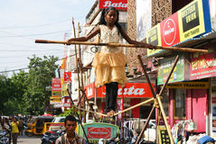 Street circus in India. A girl belonging to family circus group of tight-rope walkers  performing on the busy streets of Pondicherry, India Royalty Free Stock Image