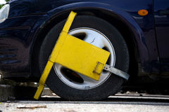 Street Clamp. Car wheel street clamped with yellow metal wheel clamp royalty free stock photo