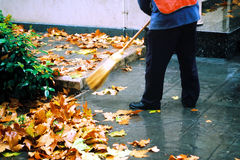 Street cleaner. Autumn street cleaner.A city worker steam-cleans the sidewalk royalty free stock images