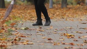 Street cleaner in shabby boots sweeping dry leaves in autumn park, low paid job. Stock footage stock video footage
