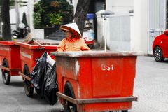 Street cleaner on street in Saigon. Street cleaner wheeling three red bins through the streets of Saigon, Vietnam Stock Images