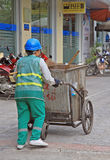 Street cleaner is wheeling trolley with garbage in Royalty Free Stock Photography