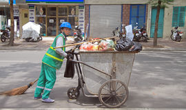 Street cleaner is wheeling trolley with garbage in Royalty Free Stock Image