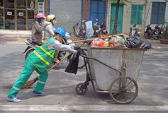 Street cleaner is wheeling trolley with garbage in Stock Photo