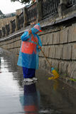 Street cleaner works with a broom on a rainy day in Moscow Royalty Free Stock Photo