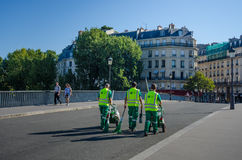 Street cleaners with brooms and carts in Paris. PARIS, FRANCE AUGUST 22, 2015  Three sanitation workers cross the St. Louis Bridge to the St. Louis Island with Royalty Free Stock Photos