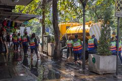 Street cleaners washing the pavements. Bangkok,Thailand - 6th March 2017: Street cleaners washing the pavements on Sukhumvit Road. The authorities do this on a stock photo