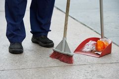 Street cleaning and sweeping with broom. Process of urban street cleaning sweeping. Worker with broom and dust pan Stock Photography