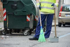 Street cleaning and sweeping with broom. Process of urban street cleaning sweeping. Worker with broom and dust pan Stock Photo